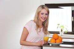 Beautiful young woman preparing fresh orange juice Stock Images