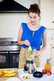 Beautiful young woman preparing juice Royalty Free Stock Images
