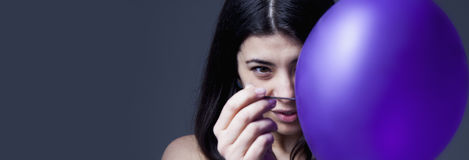 Beautiful young woman preparing to pop balloon as a symbol of di. Sappointment and ruined illusions Gestures, psychology, metaphor, body language concept royalty free stock photos
