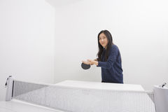 Beautiful young woman preparing to serve table tennis ball Royalty Free Stock Image