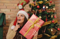 Beautiful young woman with present box in santa hat for Christma Stock Photo
