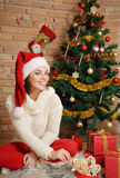 Beautiful young woman with present boxes and cookies in Santa ha Royalty Free Stock Image