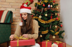 Beautiful young woman with present boxes in santa hat for Christ Royalty Free Stock Photos