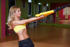 Beautiful young woman presenting a TRX exercise Royalty Free Stock Photography