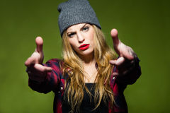 Beautiful young woman pretending to shoot gun with fingers. Stock Photo