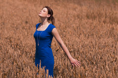 Beautiful young woman with pretty dress kisses warm summer sun. The beauty of summer. The blue of the dress is the only blue in the picture. Perfect for Royalty Free Stock Photography