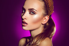 Beautiful young woman with professional makeup on purple backgro Royalty Free Stock Photography