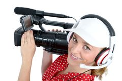 Beautiful young woman with a professional video camera and headp. A beautiful young woman with a professional video camera and headphone Royalty Free Stock Photos
