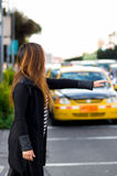 Beautiful young woman with protective mask on the street asking fo a taxi, with a blurred taxi behind Royalty Free Stock Photos