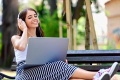 Beautiful young woman in public park working on laptop computer listening music Stock Photography