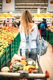 Woman pulls full trolley at the supermarket. stock photography