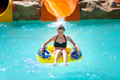 Beautiful young woman pulls off the slides in water park Stock Photo