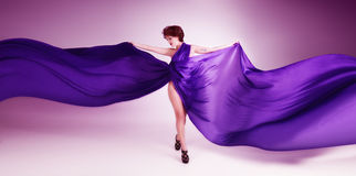 Beautiful young woman in purple dress Stock Image