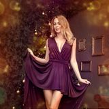 Christmas girl with purple fashion dress inside stock images