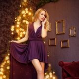 Christmas girl with purple fashion dress inside royalty free stock photos