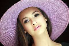 Beautiful Young Woman with Purple Hat. Beautiful and exotic young woman of multiple ethnicity wearing a purple hat with a black background royalty free stock photo