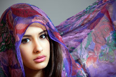 Beautiful Young Woman Purple Shawl. Beautiful and exotic young woman of multiple ethnicity wearing a blue/purple shawl over her head stock images