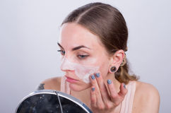 Beautiful young woman puts scrub cream on her face. Stock Image