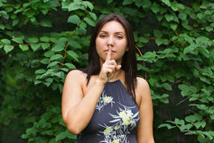 Beautiful young woman putting forefinger to lips. In a summer green Park Royalty Free Stock Photography