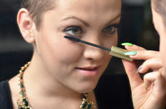 Beautiful young woman putting make up in front of old mirror Royalty Free Stock Photography