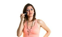 Beautiful young woman putting on make-up Stock Photos