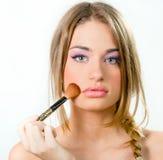 Beautiful young woman putting on makeup Royalty Free Stock Photos