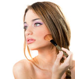 Beautiful young woman putting on makeup Royalty Free Stock Images