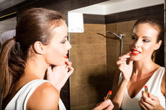 Beautiful young woman putting on makeup in the bathroom Royalty Free Stock Images