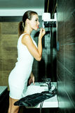 Beautiful young woman putting on makeup in the bathroom Stock Images