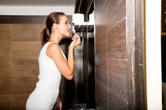 Beautiful young woman putting on makeup in the bathroom Stock Image