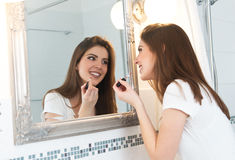 Beautiful young woman putting on makeup Stock Photo