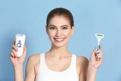 Beautiful young woman with razor and epilator. On color background Stock Photos