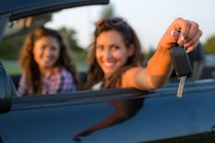Beautiful young woman reaching out car keys to the camera while royalty free stock photo