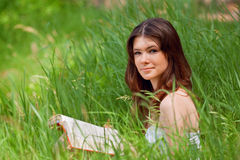 Beautiful young woman reading. A book on park stock image