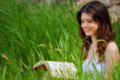 Beautiful young woman reading. A book on park royalty free stock photos