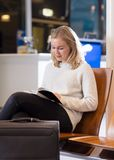 Woman Reading Book In Airport Waiting Area. Beautiful young woman reading book in airport waiting area stock photo