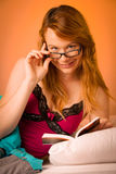 Beautiful young woman reading book in bed Royalty Free Stock Image
