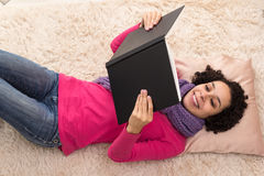 Beautiful young woman is reading a book with a black cover. Stock Images
