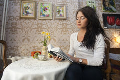 Beautiful young woman reading book in cafe Stock Photos