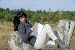 Beautiful young woman reading book in fall stock images