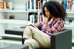 Beautiful young woman reading a book in the library. Royalty Free Stock Images