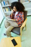 Beautiful young woman reading a book in the library. Royalty Free Stock Photo