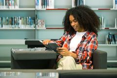 Beautiful young woman reading a book in the library. Royalty Free Stock Image