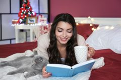Beautiful young woman reading book while lying  on bed with cute cat. Beautiful young woman reading book while lying on bed with cute cat Royalty Free Stock Photos