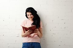 Beautiful young woman reading book near brick white wall. Royalty Free Stock Image