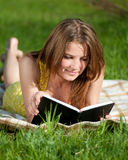 Beautiful young woman reading book outdoor Royalty Free Stock Photography