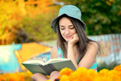 Beautiful young woman reading a book outside Royalty Free Stock Photo