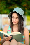 Beautiful young woman reading a book outside Stock Photos