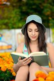 Beautiful young woman reading a book outside Royalty Free Stock Photos