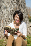 Beautiful young woman reading a book outside Stock Images